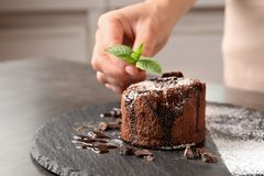 Chef decorating delicious fresh chocolate fondant. With mint at table. Lava cake recipe Stock Photography