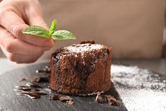 Chef decorating delicious fresh chocolate fondant. With mint at table. Lava cake recipe Royalty Free Stock Images