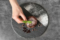 Chef decorating delicious fresh chocolate fondant. With mint at table, top view. Lava cake recipe Stock Images