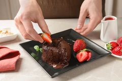 Chef decorating delicious fresh chocolate fondant. With strawberry at table. Lava cake recipe Royalty Free Stock Images