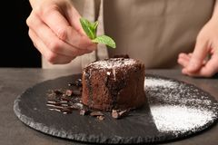 Chef decorating delicious fresh chocolate fondant with mint at table. Lava cake recipe Royalty Free Stock Photos