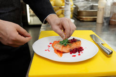 Chef is decorating fried salmon steak with herbs Royalty Free Stock Photos