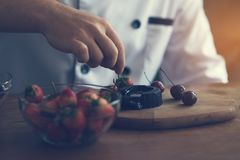 Chef decorating homemade chocolate with strawberry in kitchen.. royalty free stock photos