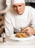 Chef decorating pasta salad with herbal leaves Stock Photo
