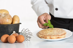 Chef decorating a potato omelette Royalty Free Stock Image