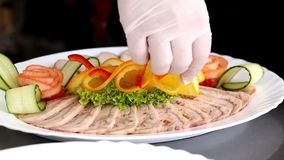 A chef decorating sliced meat and chicken roulade dish, at a restaurant kitchen stock video footage