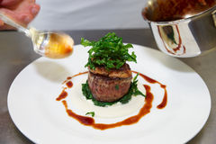 Chef is decorating steak with sauce Royalty Free Stock Image