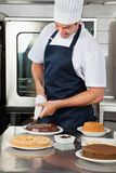 Chef decorating sweet food with piping bag Stock Images