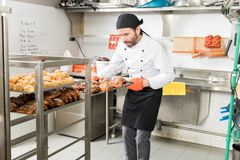 Chef With Delicious Breads In Kitchen. Male baker arranging baking sheets full of freshly baked breads in kitchen stock photography
