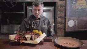 Chef in den schwarzen Kocherhandschuhen, die auf Pittabrot gegrilltem Fleisch, geschnittene Stücke gebratener Mais, Ingwer, Soßen stock video