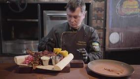 Chef in den schwarzen Kocherhandschuhen, die auf Pittabrot gegrilltem Fleisch, geschnittene Stücke gebratener Mais, Ingwer dienen stock video footage
