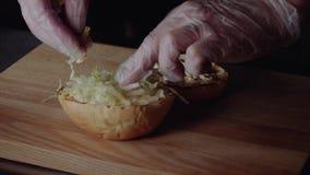 Chef, der Burger macht das Brötchen auf dem Grill braten, den Kopfsalat setzend stock footage