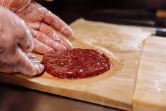 Chef, der Burger macht Chef in den Nahrungsmittelhandschuhen macht Kotelett Koteletts werden im Stahlring in einem sogar Medaillo lizenzfreies stockfoto