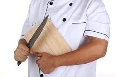 Chef, der den Holzklotz und das Messer hält Stockbild