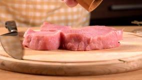 Chef, der die Wegwerfhandschuhe würzen Schweinefleisch trägt stock footage