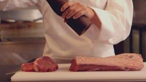 Chef, der ein Stück Rindfleisch würzt stock footage