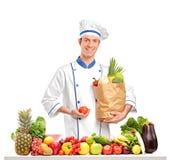 Chef, der eine Tomate und eine Tasche hinter einer Tabelle voll von den Früchten anhält und Stockfotos