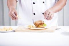 Chef, der einen Burger zubereitet Lizenzfreie Stockfotos