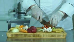 Chef, der frisches und köstliches Gemüse für das Kochen schneidet stock footage