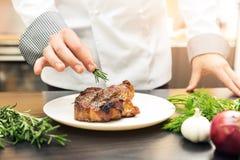 Chef, der gebratenes Fleisch mit Kräutern verziert stockfotografie