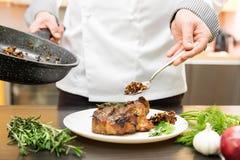 Chef, der gebratenes Fleisch mit Pilzsoße verziert lizenzfreies stockfoto