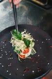 Chef, der gesunden Salat auf einem Schwarzblech mit Pinzette beendet fast servierfertig es auf einer Tabelle lizenzfreie stockbilder