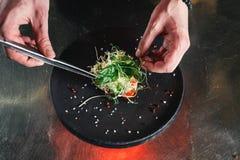 Chef, der gesunden Salat auf einem Schwarzblech mit Pinzette beendet fast servierfertig es auf einer Tabelle lizenzfreies stockfoto