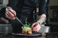 Chef, der gesunden Salat auf einem Schwarzblech mit Pinzette beendet fast servierfertig es auf einer Tabelle stockbild