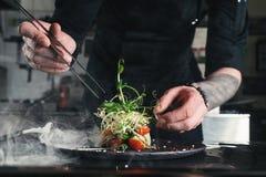 Chef, der gesunden Salat auf einem Schwarzblech mit Pinzette beendet fast servierfertig es auf einer Tabelle stockbilder