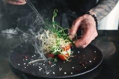 Chef, der gesunden Salat auf einem Schwarzblech mit Pinzette beendet fast servierfertig es auf einer Tabelle lizenzfreie stockfotos