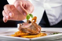 Chef in der Hotel- oder Restaurantküche kochend, nur Hände Zugebereitetes Fleischsteak mit Kartoffel- oder Selleriepfannkuchen Lizenzfreie Stockbilder