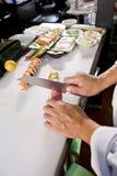 Chef in der japanischen Gaststätte, die Sushirollen vorbereitet Lizenzfreie Stockbilder