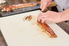 Chef, der köstlichen Aal auf weißem Brett schneidet Stockfoto