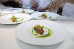 Chef, der Lebensmittel für Abendessen in der Restaurantküche kocht Stockfotos