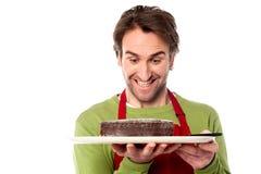 Chef, der leckeren Schokoladenkuchen hält Stockfotografie