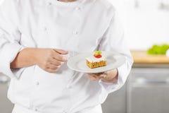 Chef, der Nachtischkuchen mit Erdbeere hält Stockfotografie