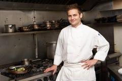 Chef, der nahe bei Kocher in der Küche steht Lizenzfreie Stockfotografie