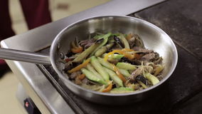 Chef, der Olivenöl mit Knoblauch Bratpfanne mit Gemüse hinzufügt stock video