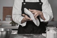 Chef, der Pizza in der Küche kocht Lizenzfreies Stockbild
