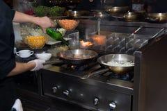 Chef in der Restaurantküche am Ofen mit der Wanne, flambe auf Lebensmittel tuend niedriges ligth selektiver Fokus Lizenzfreies Stockbild