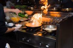 Chef in der Restaurantküche am Ofen mit der Wanne, flambe auf Lebensmittel tuend niedriges ligth selektiver Fokus Lizenzfreie Stockfotos
