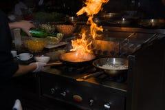 Chef in der Restaurantküche am Ofen mit der Wanne, flambe auf Lebensmittel tuend niedriges ligth selektiver Fokus Stockbild