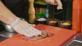 Chef, der rohes Fleisch für die Zubereitung des Steaks an der Handelsküche, Nahaufnahme mariniert Stockfoto