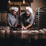 Chef, der seinen Assistenten unterrichtet, das Brot in einer Bäckerei zu backen stockfoto