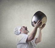 Chef, der seinen Teller in der Luft anhebt Lizenzfreies Stockfoto