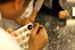Chef, der selbst gemachte Schokolade in der Küche macht Stockbilder