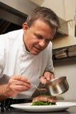 Chef, der Soße Teller in der Gaststätte hinzufügt stockfotografie