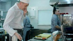 Chef, der am Telefon spricht und Bestandteile auf einer Bratpfanne in der Restaurantküche wirft stock footage