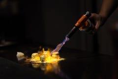 Chef, der Teller mit Gasfackel vorbereitet Lizenzfreies Stockbild