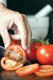 Chef, der Tomaten schneidet Lizenzfreies Stockbild